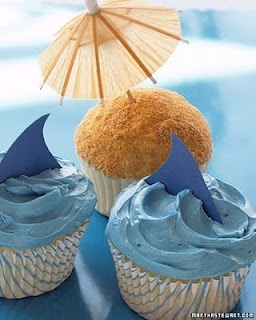 "Beach/Nautical Party: paper whale/shark fins in blue icing and cocktail umbrella in graham cracker (?) ""sand"" cupcakes"