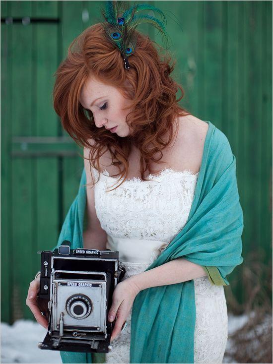 Des plumes de paon, l'oiseau que l'on voit le plus s'immiscer dans les chevelures. Cette mariée a laissé ses beaux cheveux roux et bouclés lâches. Elle porte une grande barrette qui lui retient une mèche sur le côté gauche. 3 grandes plumes de paon resserrées en bouquet sont attachées à la pince. Magnifiques, ces teintes bleu-vert, n'est-ce pas ? En plus, le châle turquoise portée sur les épaules de la mariée, par-dessus sa robe bustier, se marie à merveille avec l'accessoire de cheveux.