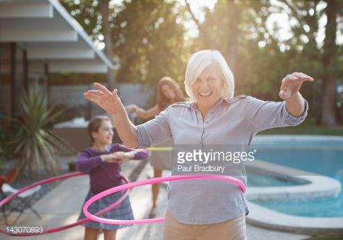 Stock Photo : Older woman hula hooping in backyard