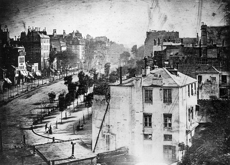 The earliest reliably dated photo­graph of a person, taken in spring 1838 by Daguerre. Though it shows Paris' busy Boul­e­vard du Temple, the long exposure time (about ten or twelve minutes) meant that moving traffic cannot be seen; however, the two men at lower left (one apparently having his boots polished by the other) remained still long enough to be dist­inctly visible.