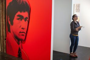 """Wing Luke Museum volunteer Liz Weber stands near the entrance to the museum's new   Bruce Lee exhibit, """"Do You Know Bruce?"""" It focuses on the martial-arts legend's time in Seattle."""