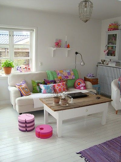 Another angle of this boho chic apartment. Gorgeous timber coffee table and pretty pops of pastels.