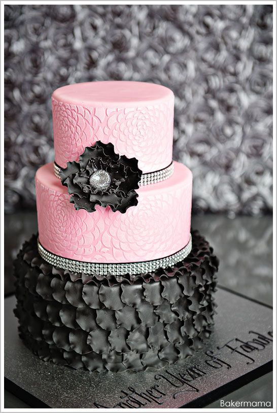 A sassy black and pink birthday cake featuring rows of ruffled petals,