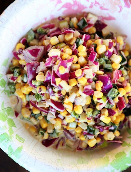 Crunchy Corn Slaw recipe with purple cabbage, poblano peppers, red onion, carrots, apple, poppyseeds, mayo, dijon)