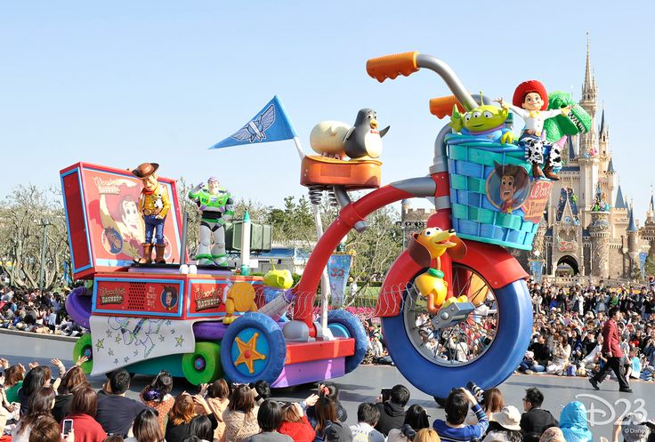 A giant tricycle, powered by characters from the Toy Story films, makes its way through the park.