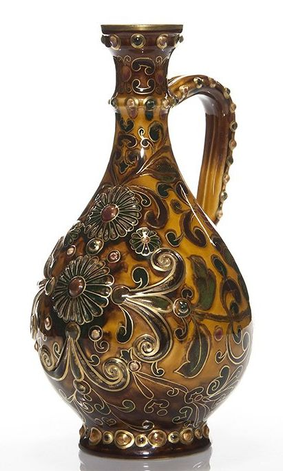 "Zsolnay Pecs pitcher in mustard brown with raised daisies and leaves amid a surround of painted flowers and leaves, enhanced by fired on gold. Height 11 1/4 inches. Impressed ""Zsolnay, 462-1"" and having the 5 towers TJM back stamp under the glaze."