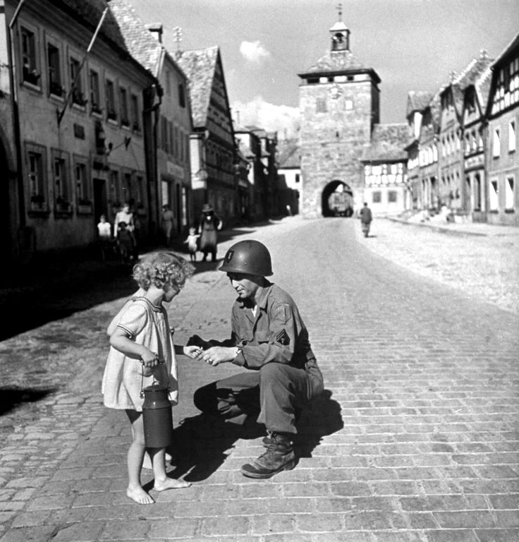 U.S. Army Supply Sgt. Ralph Gordon kneels to give barefoot German girls sticks of chewing gum following the German defeat and the beginning of the Allied occupation of Germany. Scheinfeld, Bavaria, Germany. October 1945.