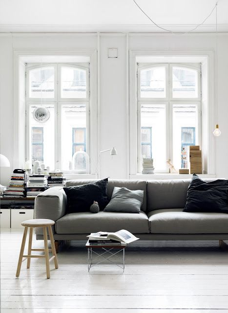 grey sofa + white wood floors + exposed diamond bulb + bare windows