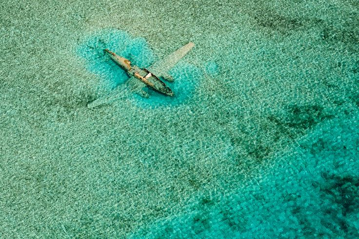 National Geographic award winning image of a ditched Curtiss C-46. While island hopping around the Bahamas in a Cessna C172 SP, I photographed this Curtiss C-46 which ditched on Nov 15, 1980. It crashed while it was on a drug smuggling mission for the Columbian Medellin drug cartel and lies in shallow water East of the Norman's Cay airport in the Exumas. Lengthy internet research paid
