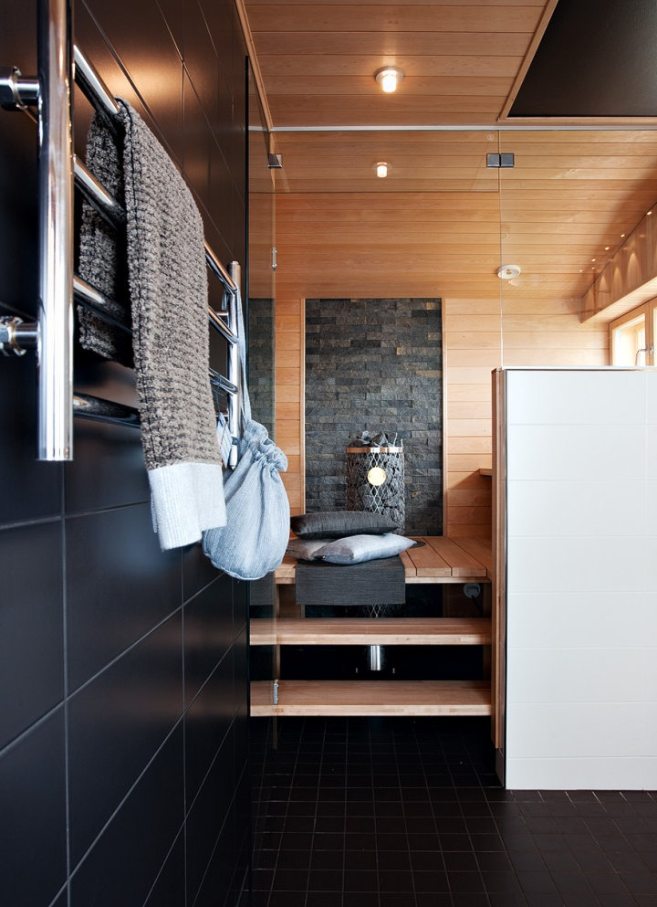 Sauna with stone, raised floor, window for natural light, glass wall.