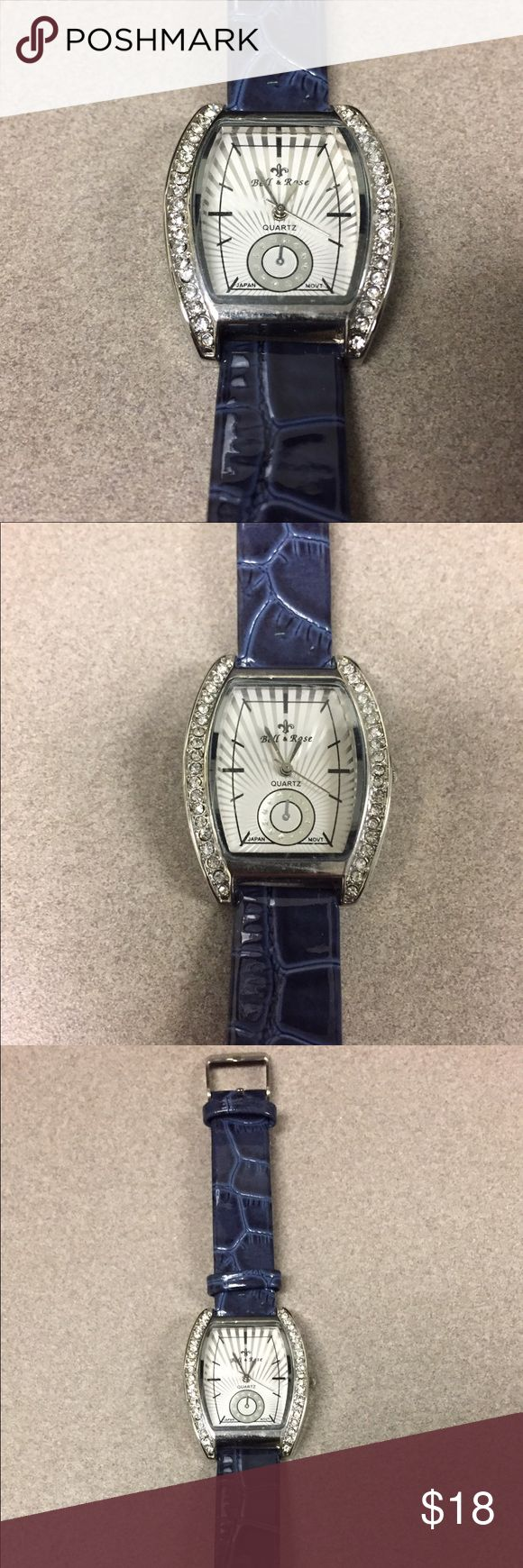 Women's Navy Blue Quartz Watch Silver & white face with tick marks for the hour positions. Face has a fleur de lis above the brand name. Adorned with crystals on the left & right side of the watch. Quartz (Japan Movement). Band is a pretty shade of navy with croc detail. Back of the face is stainless steel. Unique color in great condition! Brand new battery. Bell & Rose Accessories Watches