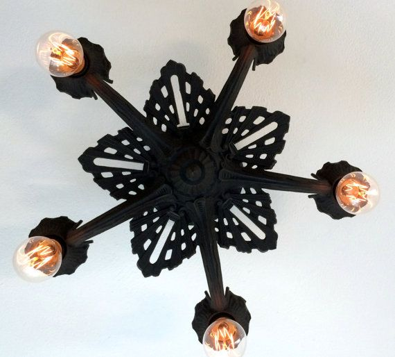 This beautiful 5 light fixture is cast in thick iron with a very art deco decor. As with many iron fixtures, the original coloring did not survive the decades and has been abrasive stripped of rust, sealed to prevent oxidation, and refinished in charcoal black. The cast iron gives testament to its quality of material. Excellent for any room!. Measures 18 inches across and extends 9 inches from ceiling to bottom of finial. The original brass encased copper and porcelain sockets are resoldered…