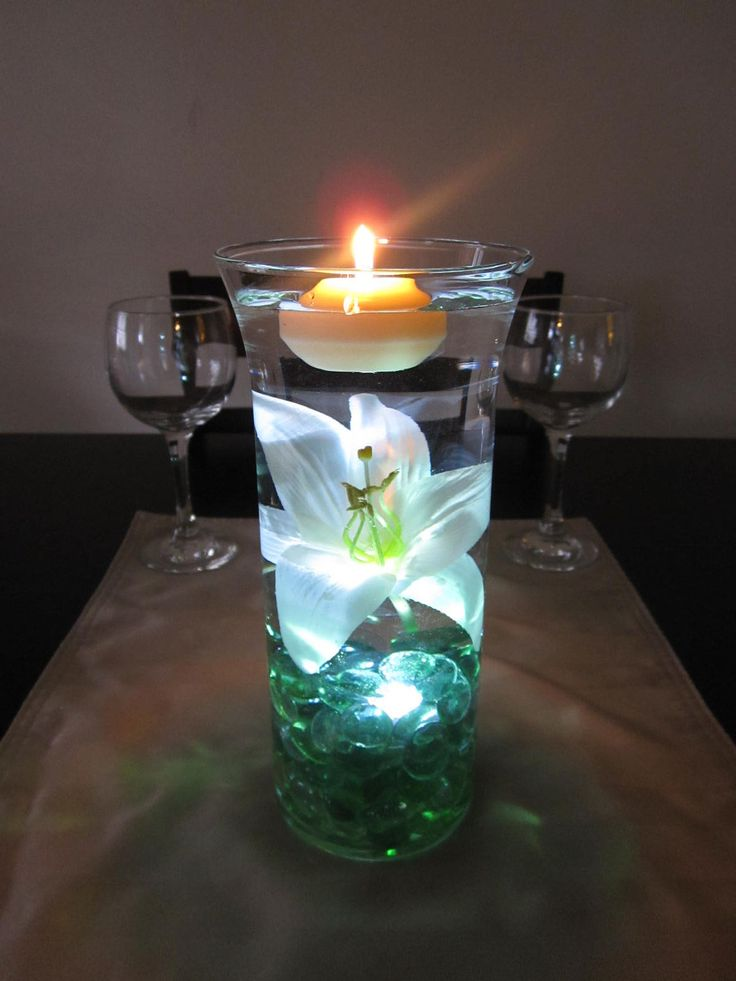 floating candle, glass beads, and floral wedding centerpiece with colored LED light at bottom