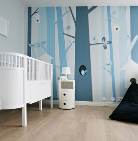 This modern tree mural is so pretty in shades of blue. The European crib is so nice paired with the modern drum table. And is that a FatBoy I spy in the corner?