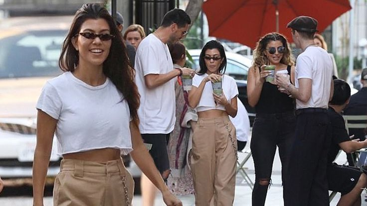 Kourtney Kardashian flashes her abs as she grabs juice with Larsa Pippen...