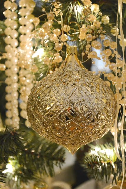Gold ornament sparkles amidst pearls and Christmas greenery