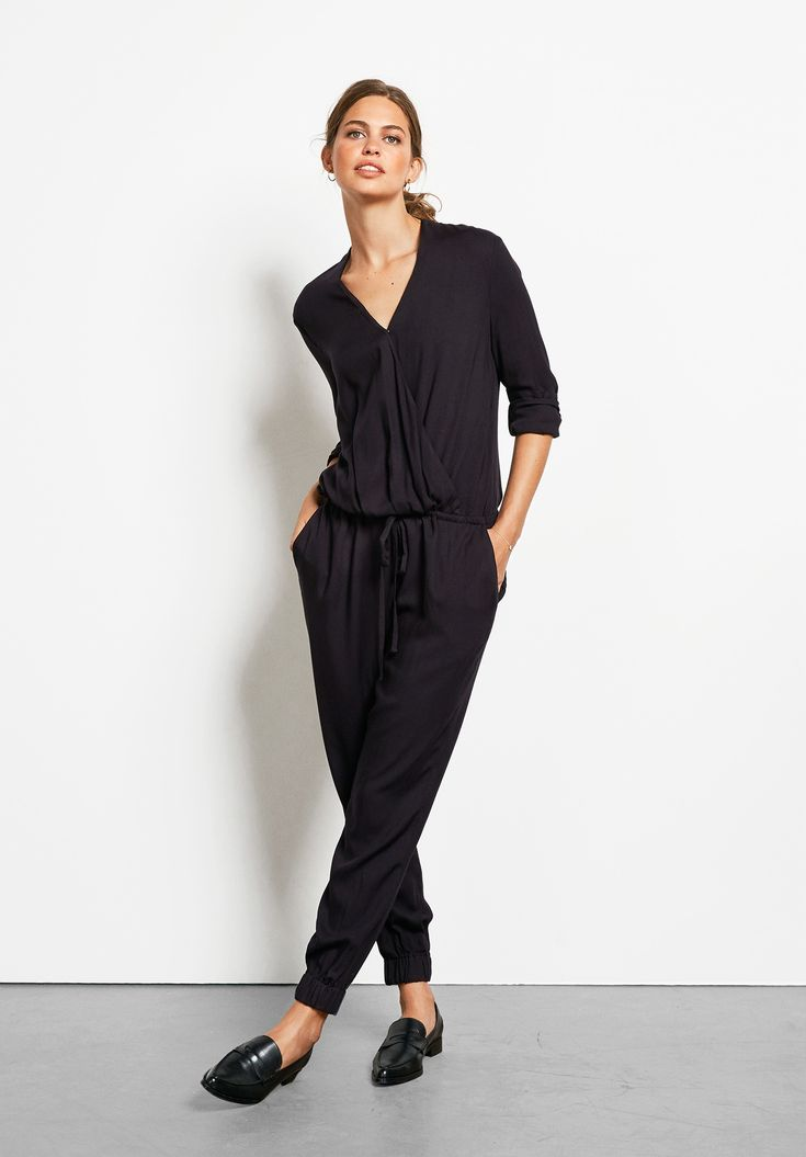 "The most elegant jumpsuit you'll wear! This all-in-one has a flattering wrap front and elasticated cuffs so you can wear with various heel heights. • True to size. • Cuff hems. • Drawstring waist. • Lightweight woven fabric. • Inside leg 68cm (size 10). • Model is 5'9"" and wears size 10."