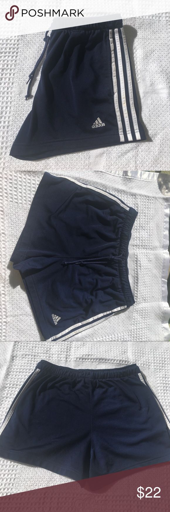 Navy blue adidas women's shorts Navy blue adidas striped shorts. They are dark blue in color with three white stripes on each side. The adidas logo is on left leg at bottom in sewn white letters. They stretch and have drawstring at waist. Size medium. In overall good condition adidas Shorts