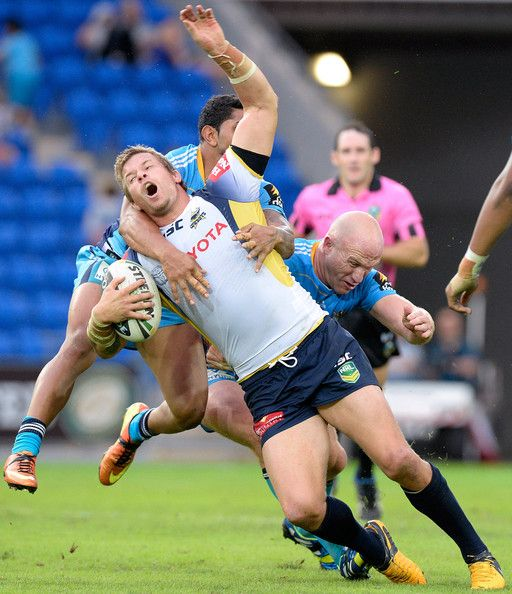 Ashton Sims of the Cowboys is hit high by Albert Kelly of the Titans during the round 12 NRL match between the Gold Coast Titans and the North Queensland Cowboys at Skilled Park on June 2, 2013 in Gold Coast, Australia.