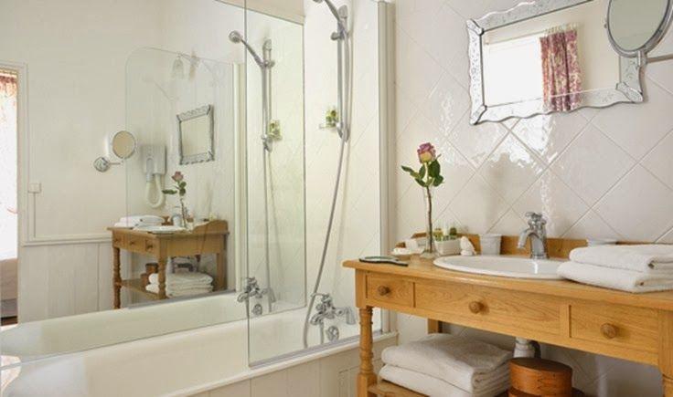bagno luminoso con un grande specchio e piccole piastrelle montate diagonalmente