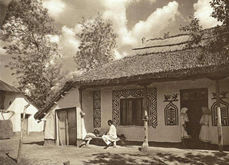 """1920's peasant house in Romania. The ancient """"tree of life"""" motif (pomul vietii) painted near the door, flanked by two birds - a sacred symbol commonly found in Pre-Christian Europe and around the world. After forced industrialization, many symbolic paintings disappeared and are still disappearing from the exterior walls, being painted over or covered with another layer of cement."""