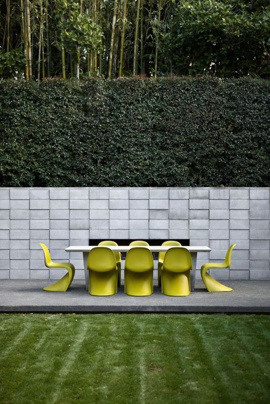 12 Ways to Use Panton Chairs: Architex designed this Auckland home. Despite the lush lawn and concrete patio complete with large dining table and eight yellow Panton chairs, it's actually located in the city.