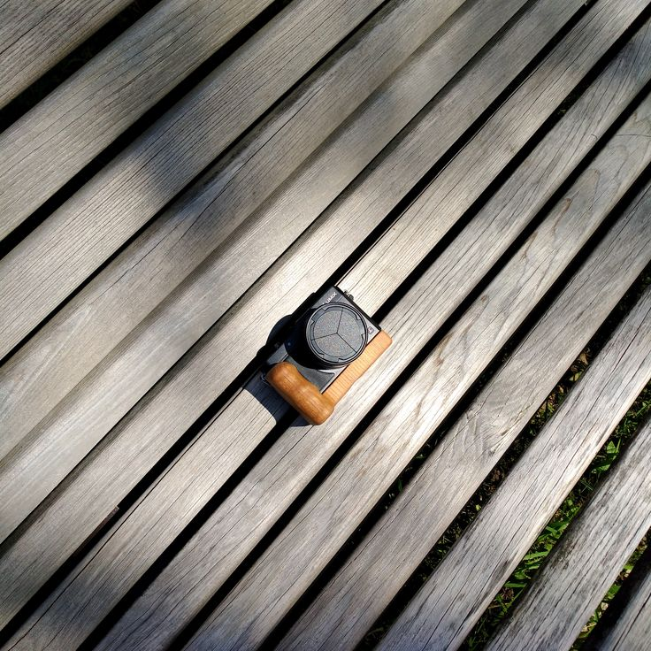 Holzgriff wooden camera grip on a Panasonic Lumix LX100 on a bench