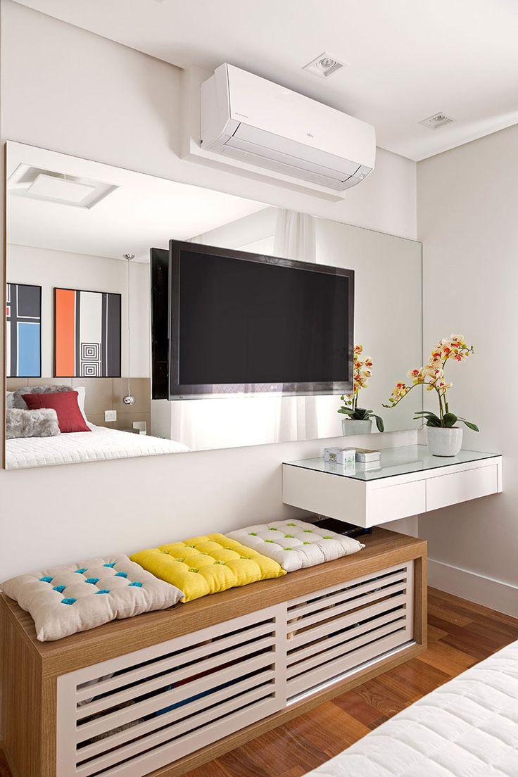 Decoração de apartamento colorido. No quarto de casal obras de arte, pendente, almofadas vermelhas e flores.