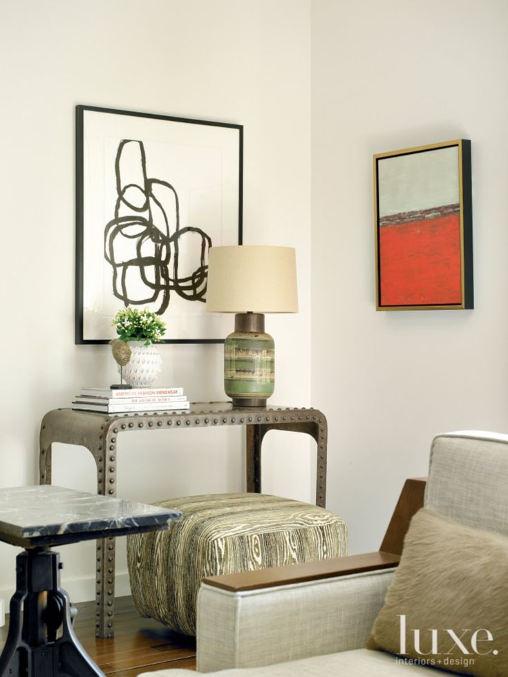 A vintage steel console table anchors a corner in the living room, where an  ottoman from Dakota Jackson is tucked away for occasional use. from luxe.