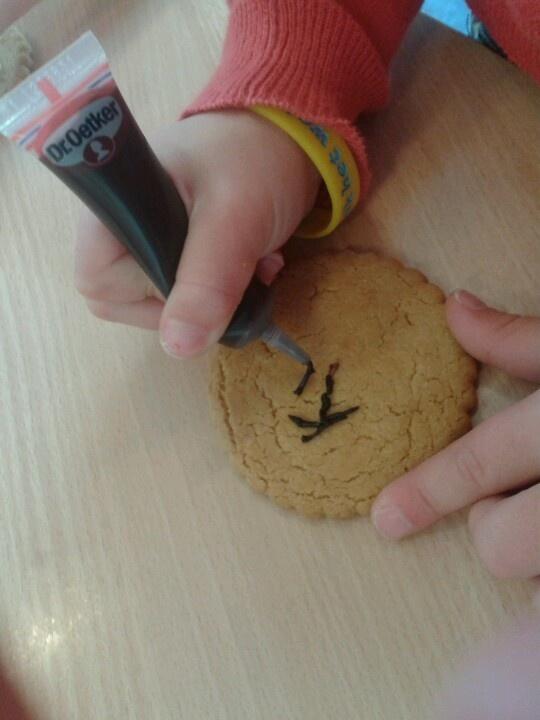 Bij het leren van het woordje koek schrijven we met eetstiften het woordje op koek.