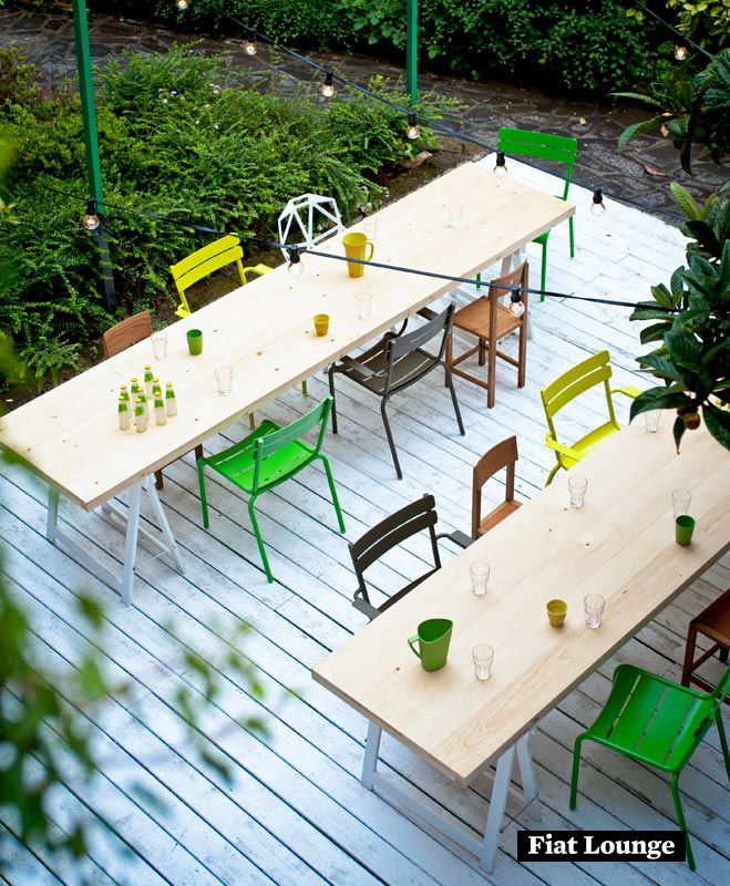 Kleurrijke stoelen van Fermob en ruimtelijke tafels met schragen op veranda