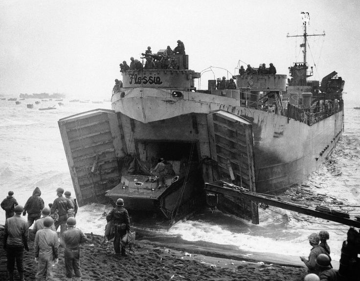 Striking images from the battle of Iwo Jima: Flat Nose Flossie, a Coast Guard manned LST buries its nose in the volcanic sands of Iwo Jima beachhead, Japan on Feb. 27, 1945, while elements of a Marine Corps amphibious tractor unit unload cargo under protection of forward guns
