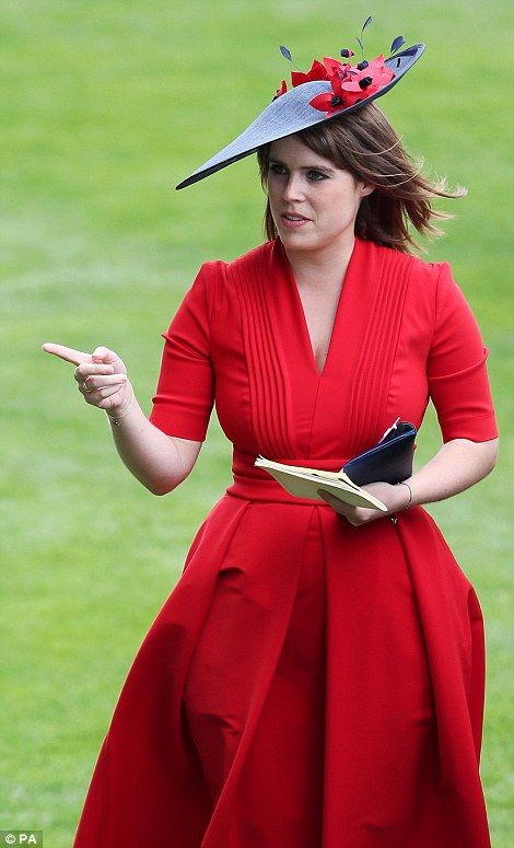 Princess Eugenie gestures as she strolls through the parade ring at Royal Ascot...