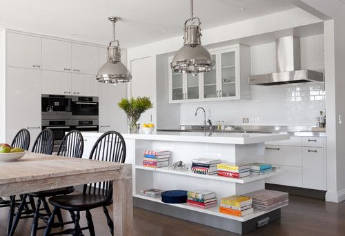 A rustic farmer's table from Boyd Blue surrounded by Windsor chairs adds warmth and contrasts with the all-white kitchen and metallic sheen of the fixtures and Ralph Lauren pendants. By Diane Bergeron Interiors (Houzz, October 2012)