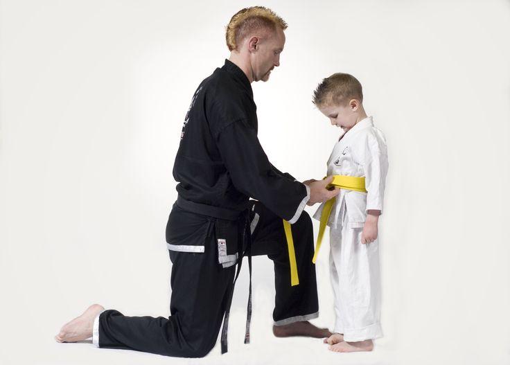 Sensei Trevor helping a Little Dragon tie his belt.