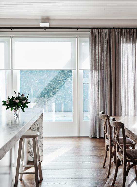 layered semisheer roller shades with sheer drapes