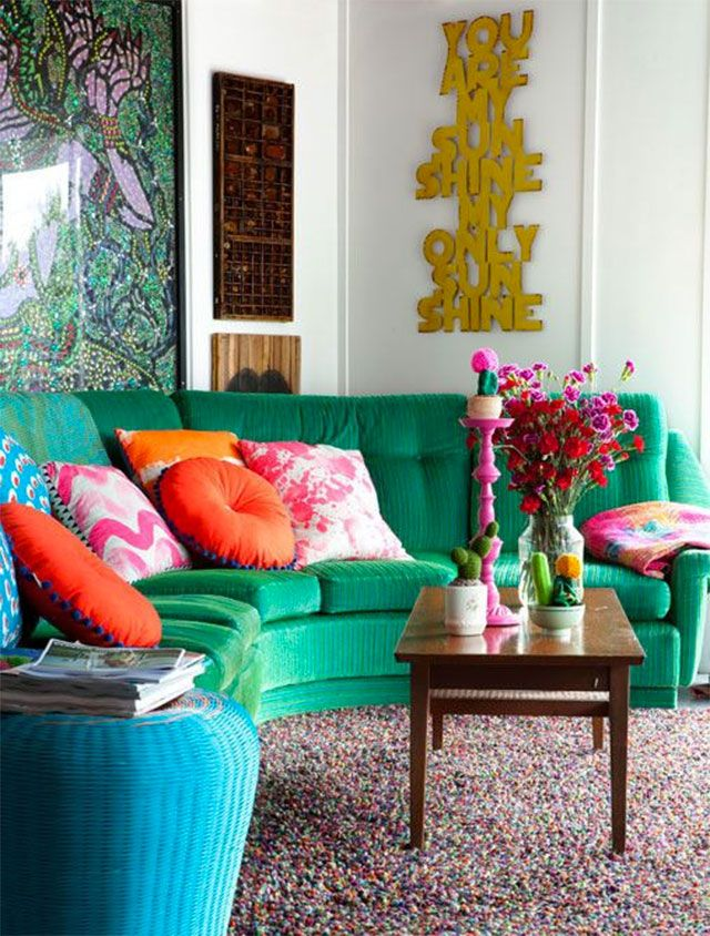 Sofá seccional de tela verde. Cojines contrastantes en colores anaranjados, calipsos y fucsias.
