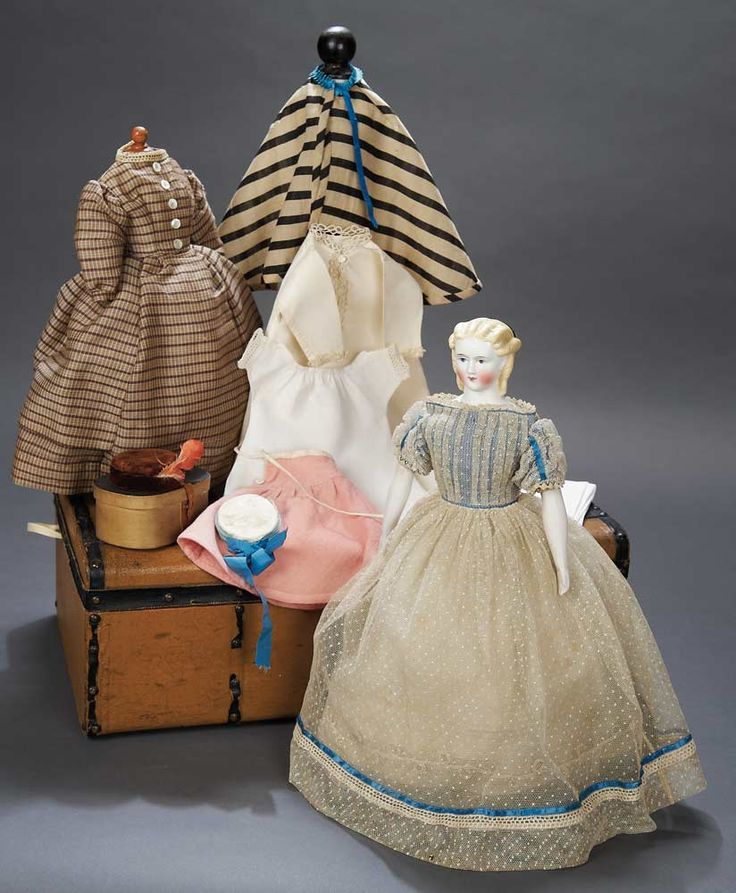 Doll, circa 1870. Doll with original body,wearing original dotted tulle gown with blue silk trim,undergarments,along with trunk,wooden hat box,undergarments,lovely silk gown,cape.