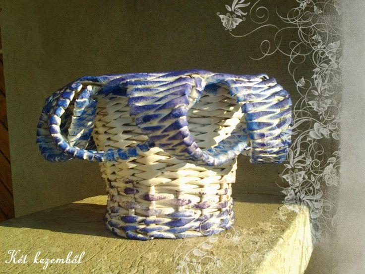 Fehér virágkaspó, kék és lila díszítő festéssel. Különlegessége, hogy a felső perem eldolgozása teljesen rendhagyó.