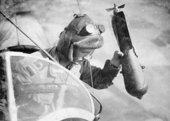 Hand bomber - A crewman on a British airship prepares to drop a bomb from the rear cockpit during WWI. Undated