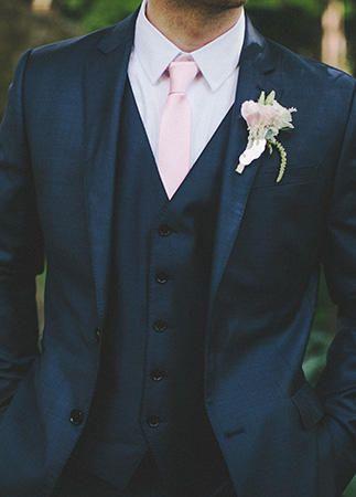 Un traje clásico azul con un toque rosado queda perfecto para una ceremonia de día