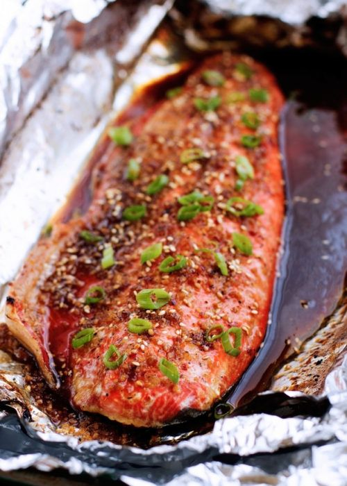 A quick and easy salmon in foil recipe. This asian inspired sesame ginger salmon baked in foil is tender and flakey. Brushed with honey sesame ginger sauce.