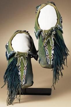 Southwest, Kiowa Painted and Fringed Moccasins, circa 1885. This pair features native tanned and painted deerskin uppers with rawhide soles. The moccasins are characterized by hide fringe extending along the outer side of the vamps, long heel fringe, short bifurcated tongues, and rectangular shaped cuffs. They are painted a deep green overall, the vamp and heel fringe done in dark blue.