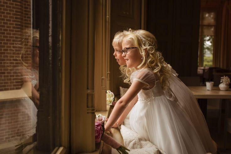 2 mooie bruidsmeisjes kijken naar het bruidspaar. Wat een mooie foto!! Ze hebben een prachtige kleding aan van Corrie's bruidskindermode. Heb jij binnenkort ook een bruiloft en heb je ook bruidskinderen erbij? Kijk dan snel op bruidskindermode.nl voor stijlvolle kleding voor bruidsmeisjes en bruidsjonkers. En natuurlijk zijn er ook bijpassende accessoires. Trouwdag, huwelijk, bruiloft, bruidsmeisjeskleding, kinderbruidsmode, kinderbruidskleding, bruidsmeisjesjurk, kinderfeestkleding.
