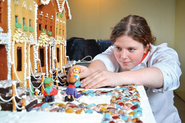 "Setting up house: Charlotte Gurney-Banning holds up the ""people"" she made for her gingerbread house. Charlotte, a high-functioning autistic student at New Westminster Secondary School, came second in her category at the Hyatt's Gingerbread Lane event."