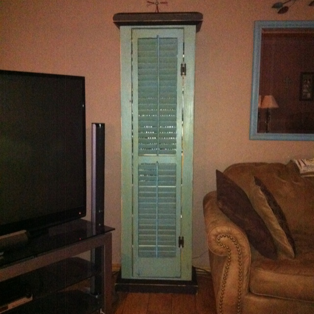 Distressed wooden cabinet made with an old wooden shutter for the door.  Makes a great video cabinet.
