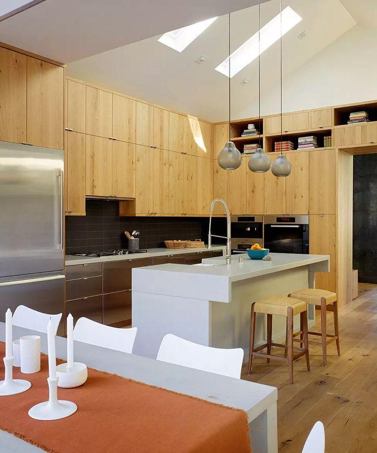 Design cucina moderna creato con mobili tutta altezza realizzati con un mix tra legno e metallo