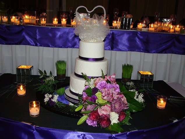 This event was planned around a purple, black and white color scheme so we introduced varying shades and tones of purple to the bouquet which made for an effective pairing with the bouts worn by the men. Note the purple fabric details in the background along the head table. This event was at the Atlantic Ballroom of the Westin Hotel, Halifax. The design and decor done by grandbeginningsdecor