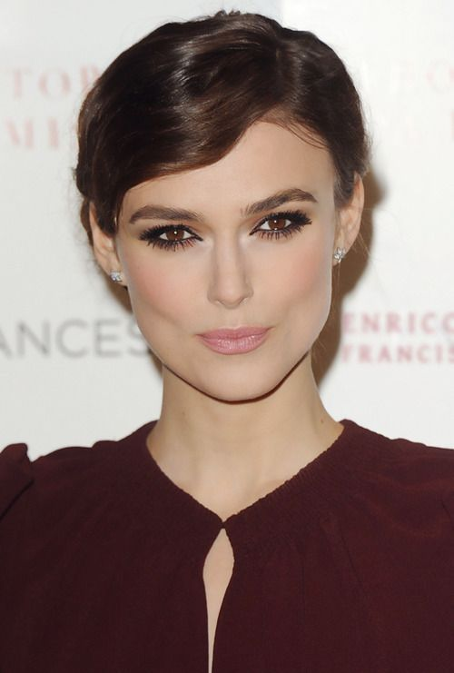 Preso com frente levemente ondulada e penteada para o lado e make belo com olho bem marcado e cantinho interno iluminado na Keira Knightley