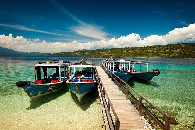 Dive boats tied up alongside the pier on Menjangan Island in north Bali, Indonesia